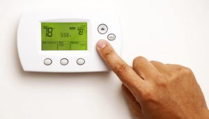Guy programming thermostat for lower energy bills